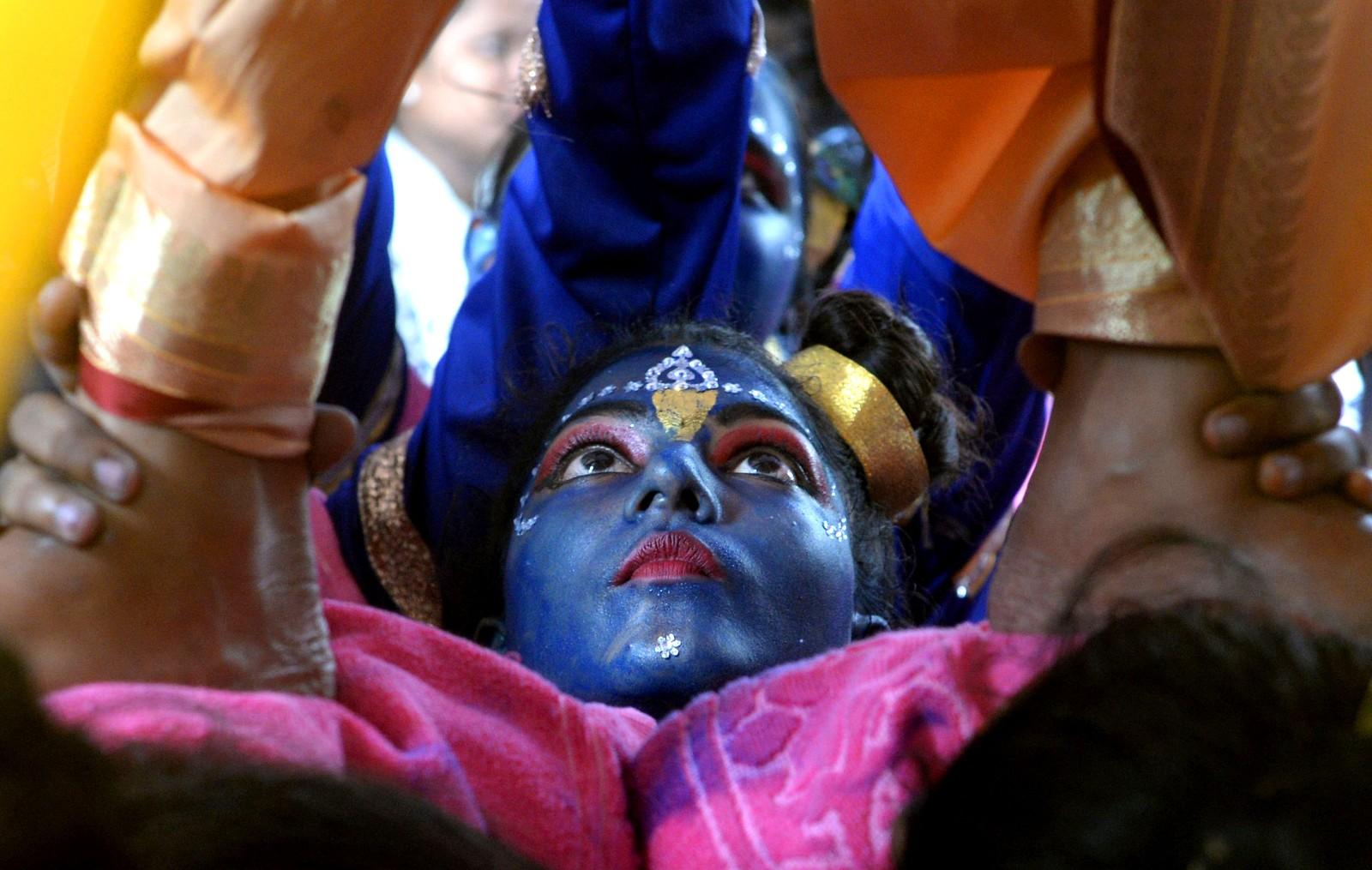 """En indisk kvinne kledd ut som den hinduistiske guden Krishna er med på å forme en menneskelig pyramide under feiringen av """"Janmashtami"""", som markerer Krishnas fødsel. Fra i år får ikke barn lov til å bli med på den populære, men potensielt farlige festivalen. Bildet er tatt den 23. august."""