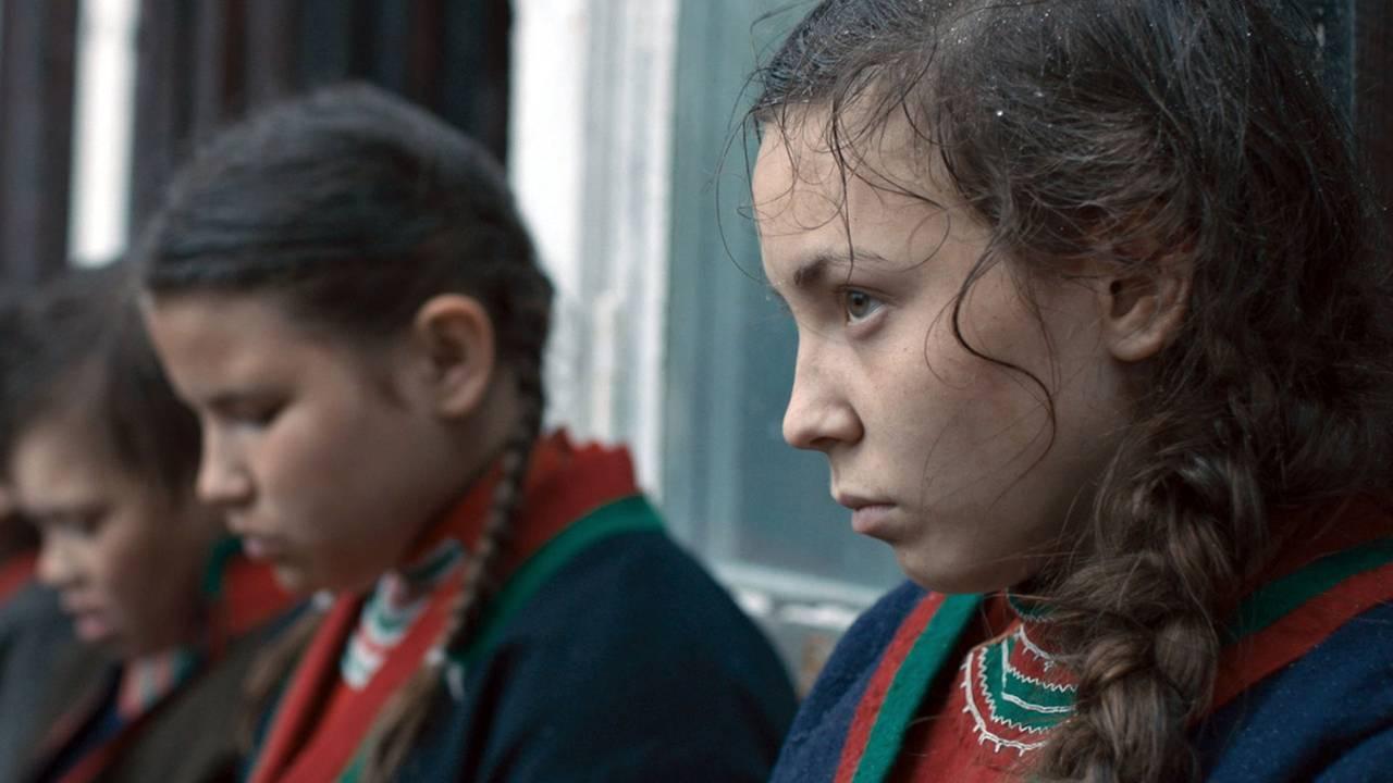 Fra filmen Sameblod. Tre jenter sitter ved siden av hverandre, sett fra siden, jenta foran ser opp på noen, de neste har blikket senket., Iført samiske klær.