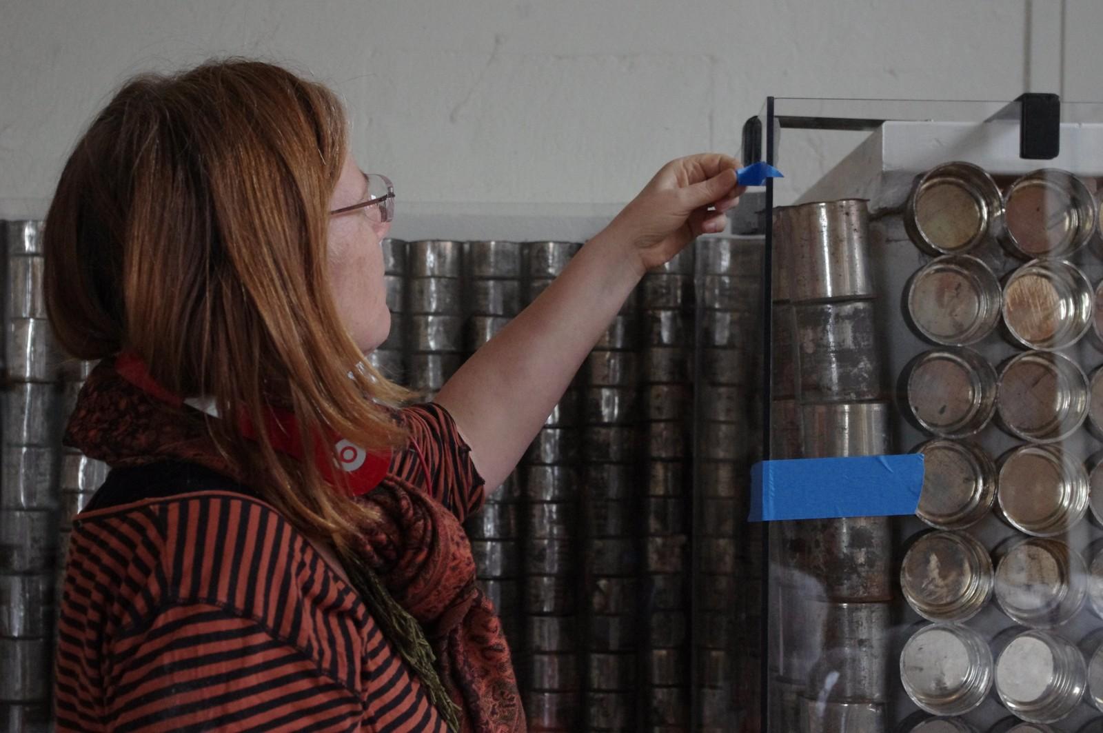 SISTE FINPUSS: Prosjektleder Inger Christine Årstad gjør siste finish på monteret med gamle melkebokser.