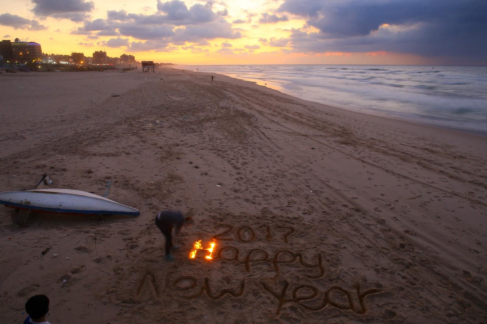 GAZA: Den palestinske kunstneren Osama Sbeata (26) tenner lys i sanden og ønsker Godt nytt år på stranden utenfor Gaza City på Gasastripen.