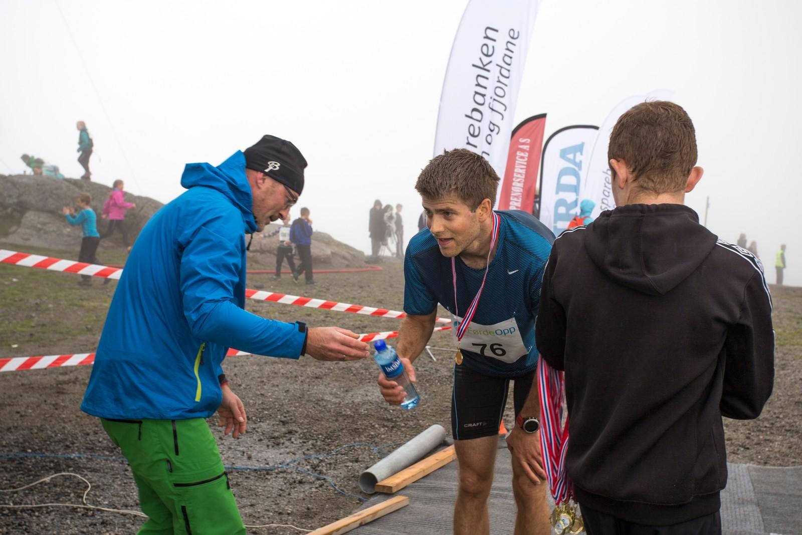 Magnus Hjartås får vatn av støttemannskapet ved målstreken.