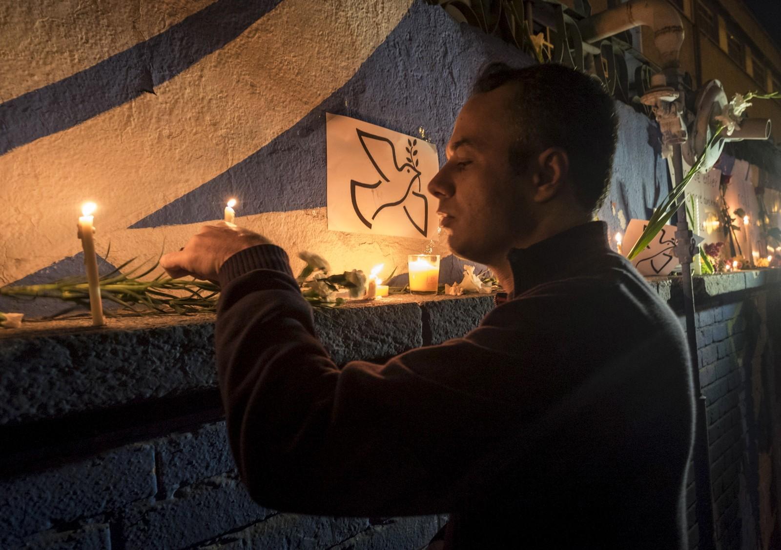En mann tenner lys ved den franske ambassaden i Teheran.