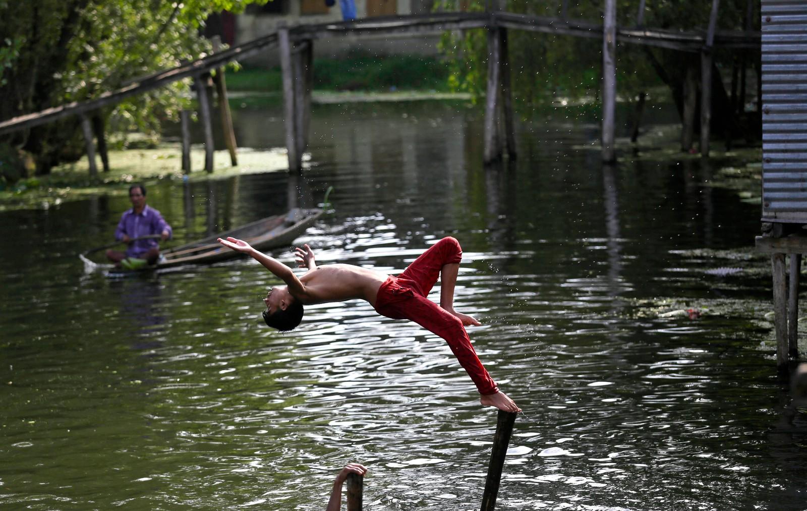 En gutt kaster seg fint ut i innsjøen Dal i Srinagar i Kashmir i India.