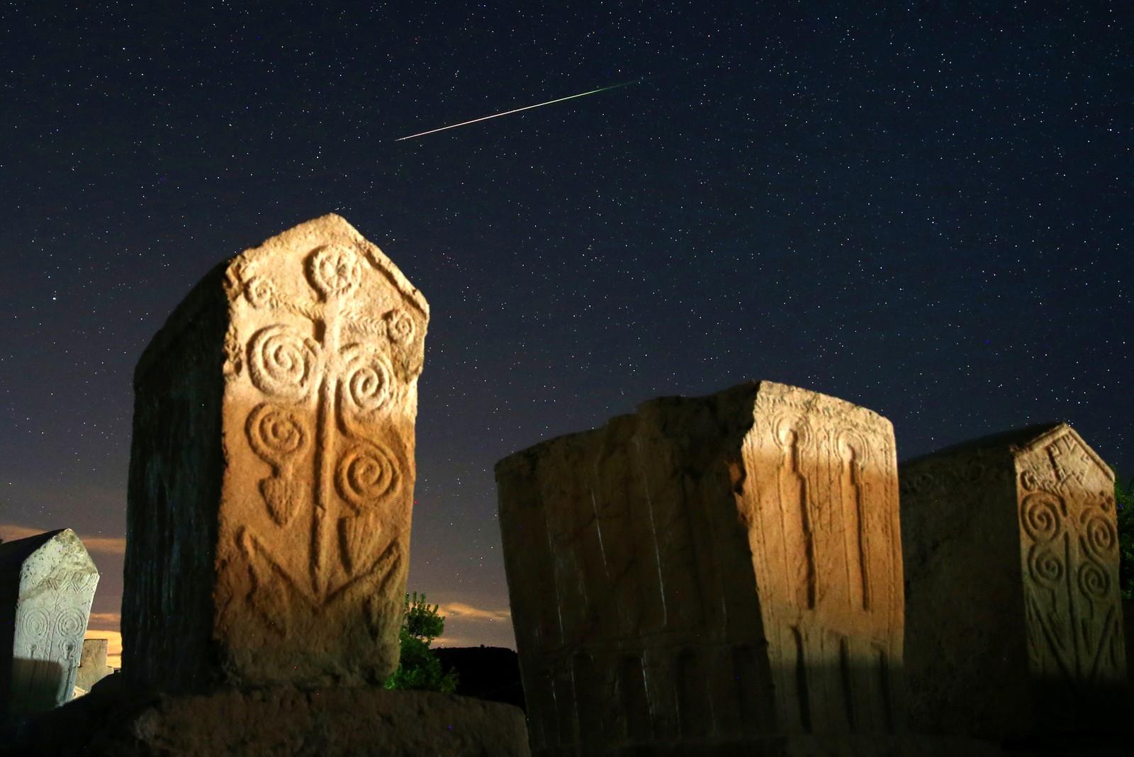"""En meteor på stjernehimmelen over gravstøtter fra middelalderen i Radimlja i Bosnia og Herzegovina den 12. august. Hvert år i august, i bare noen få dager, kan man se et lysshow på himmelen kalt """"perseidene"""". I år var det ekstra kraftig, med opptil 150-160 stjerneskudd på én time."""
