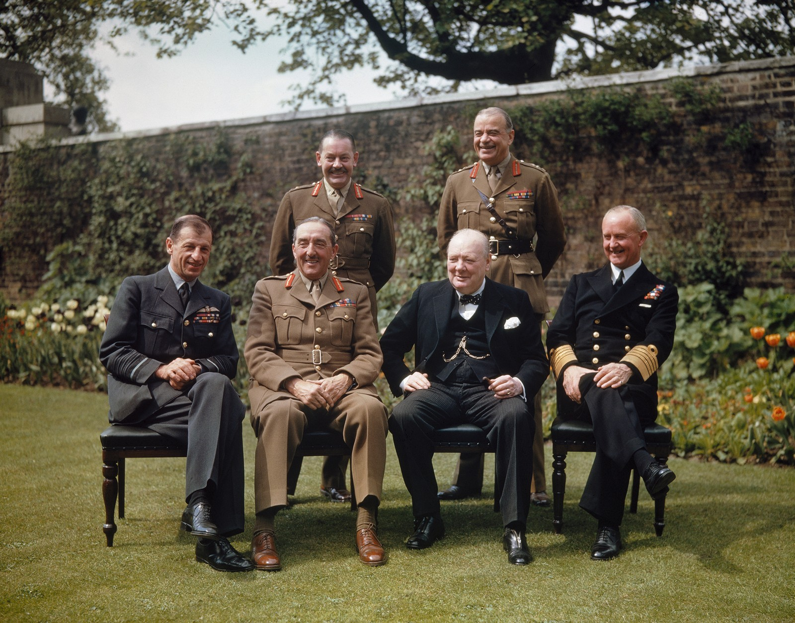 Foran fra venstre: Air Chief Marshal Sir Charles Portal; Field Marshal Sir Alan Brooke, the Rt Hon Winston Churchill; Admiral Sir Andrew Cunningham. Bak fra venstre: the Secretary to the Chiefs of Staffs Committee, Major General L C Hollis; and the Chief of Staff to the Minister of Defence, General Sir Hastings Ismay