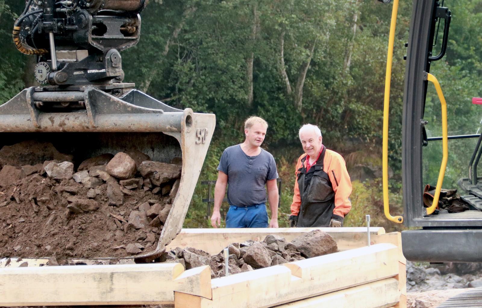FYLLER PÅ MED STEIN: For at tømmerkarene skal stå i mot vannmassene, fylles de med stein. Ordfører Knut Olav Omholt (t.v) og Ole Petter Skjerven fra Kjærra Laxefiske i bakgrunnen.