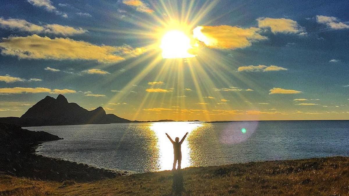 Strekker armene mot sola - Foto: Line Nilsen Olufsen/@lofoten_line/Instagram