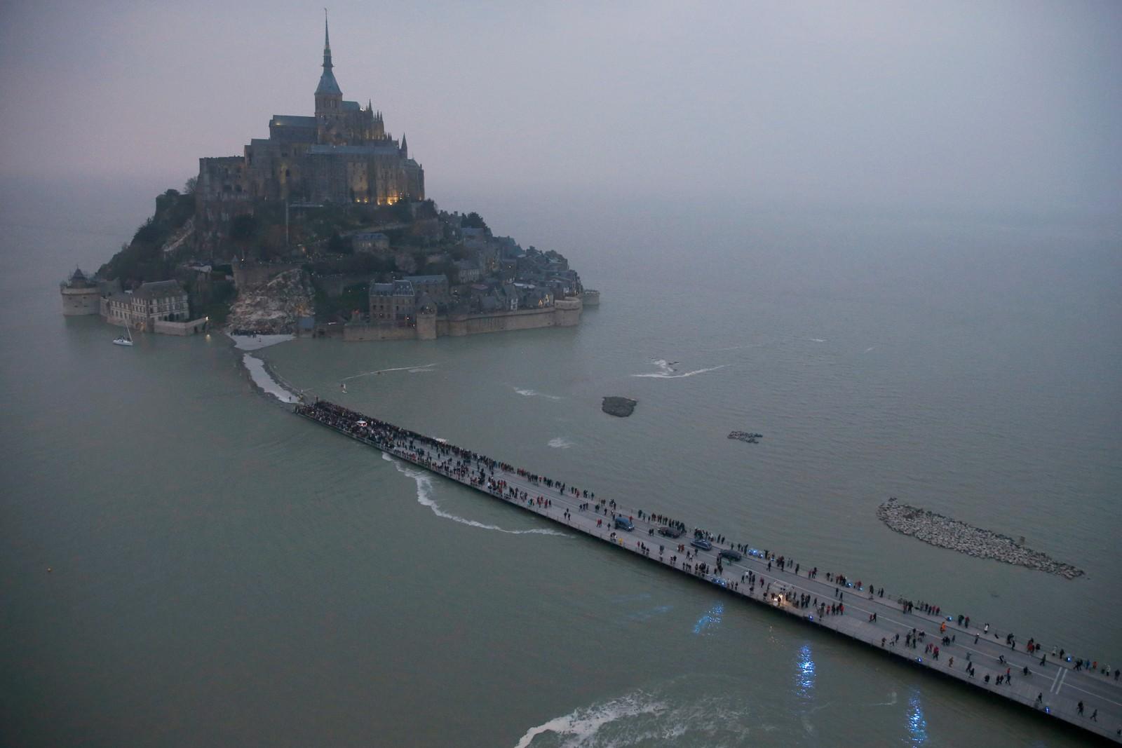 Turister samler seg på broa ut til Mont Saint Michel. Klosteret er ventet å bli nesten helt omsluttet av havet på grunn av det uvanlig høye tidevannet som er ventet.