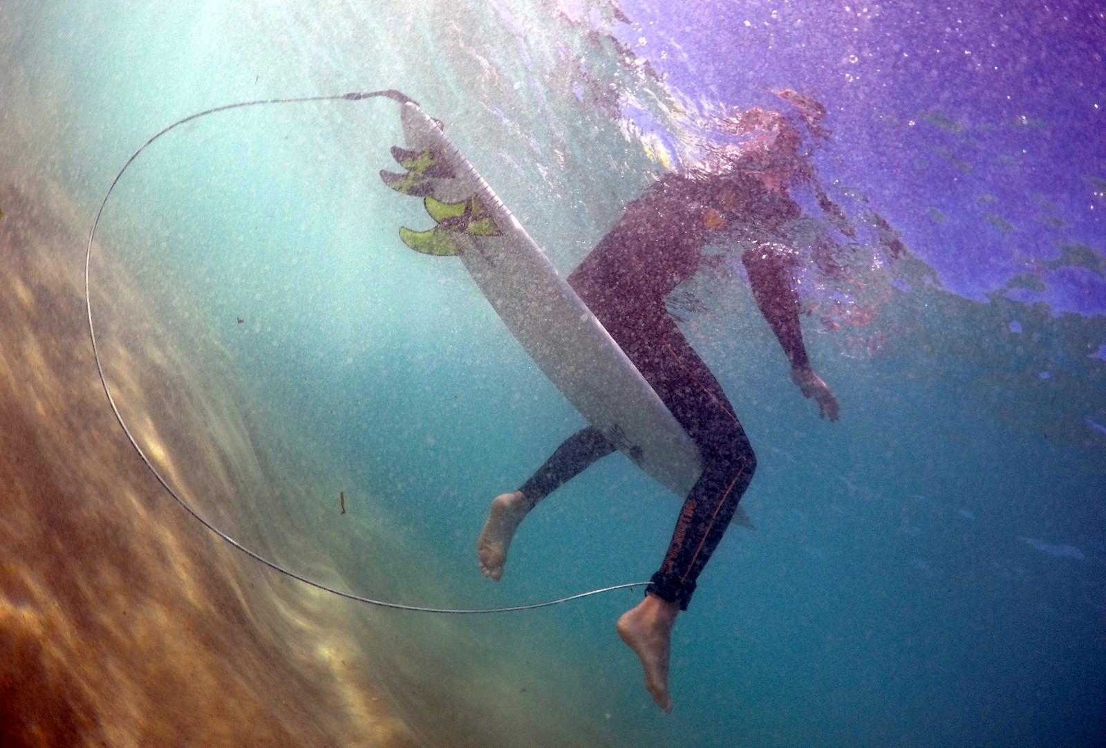 """Surfer Arlen Macpherson sitter i vannet på Bondi beach og viser fram en oppfinnelse som skal holde haier på avstand.  Flere haiangrep har skremt vekk mange surfere og Macphersons """"dings"""" er ment å skremme vekk haier ved hjelp av elektroniske signaler som forstyrrer haiens sanser."""