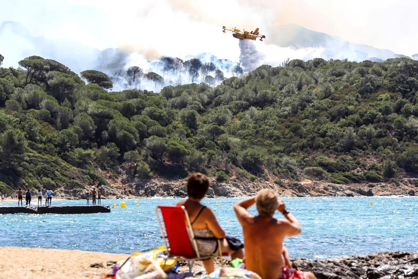 Turister tar det ganske så rolig på stranden i La Croix-Valmer i Frankrike mens et fly forsøker å bidra til å slukke en skogbrann.