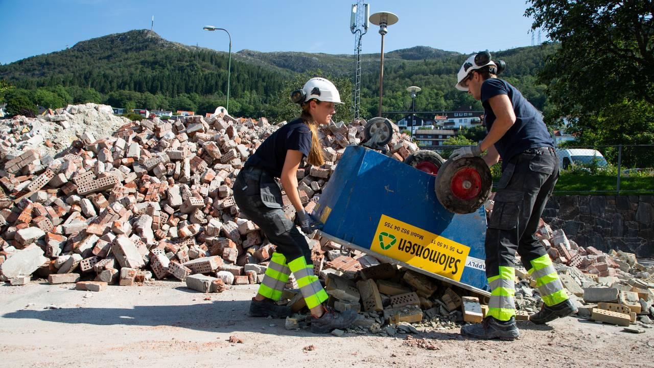 To sommervikarer tømmer en tralle med murstein. Bak ser man en stor haug med ødelagt murstein. Helt i bakgrunnen skimter man Ulriken.
