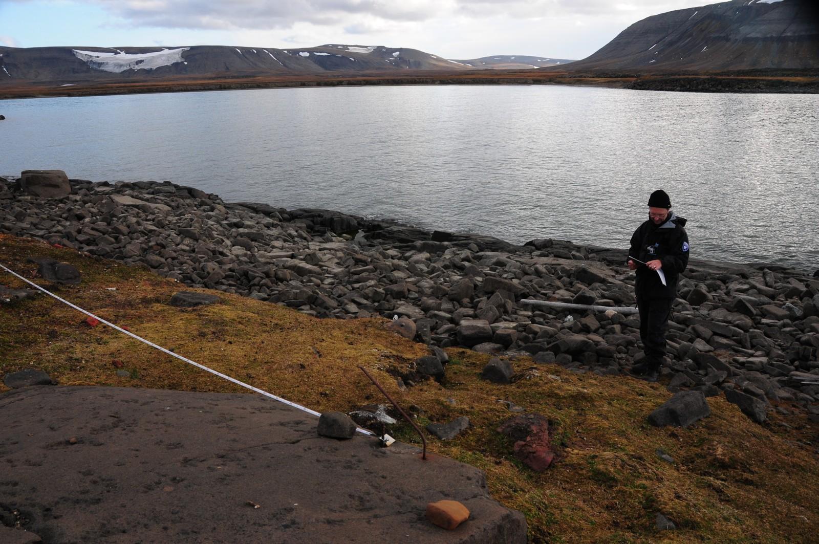Arkeolog ved Sysselmannen på Svalbard, Snorre Haukalid, måler erosjon i Habenichtbukta i 2014.