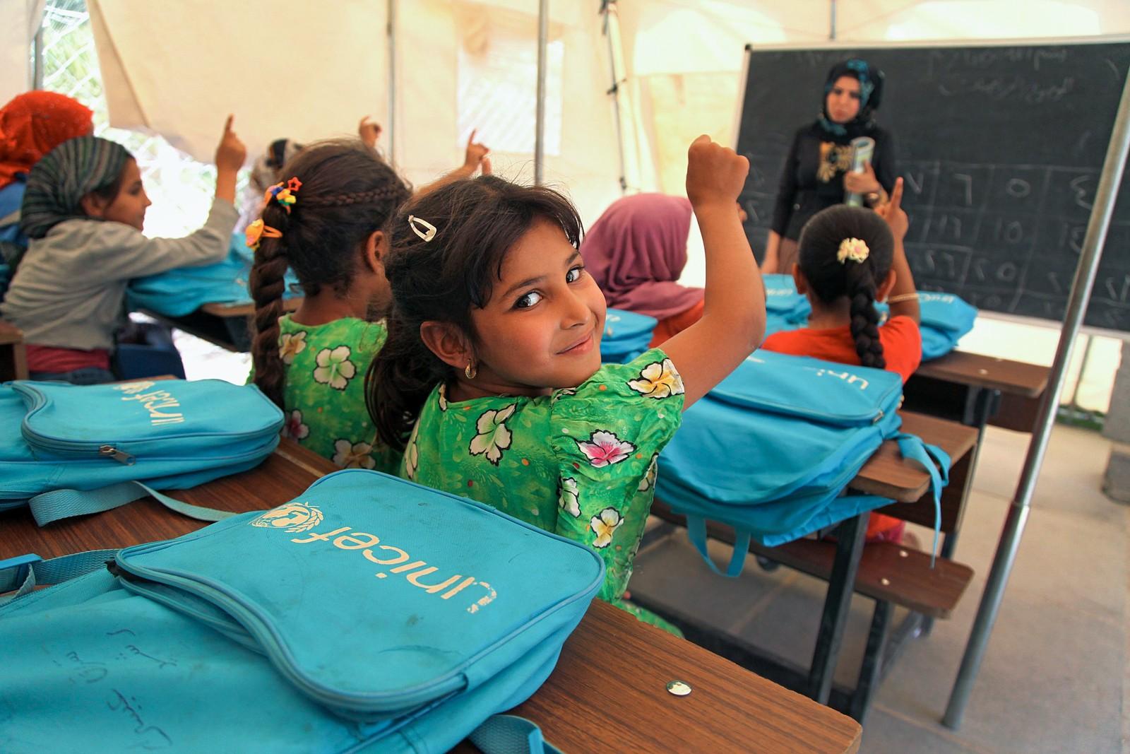 En elev holder armen i været for å svare på lærer Hiba Ahmed sitt spørsmål, i et lasterom i en teltleir nær Bagdad 16. juni, 2016.