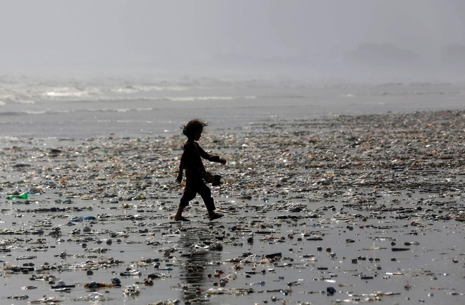 En jente går blant søppel på en strand i Karachi i Pakistan.