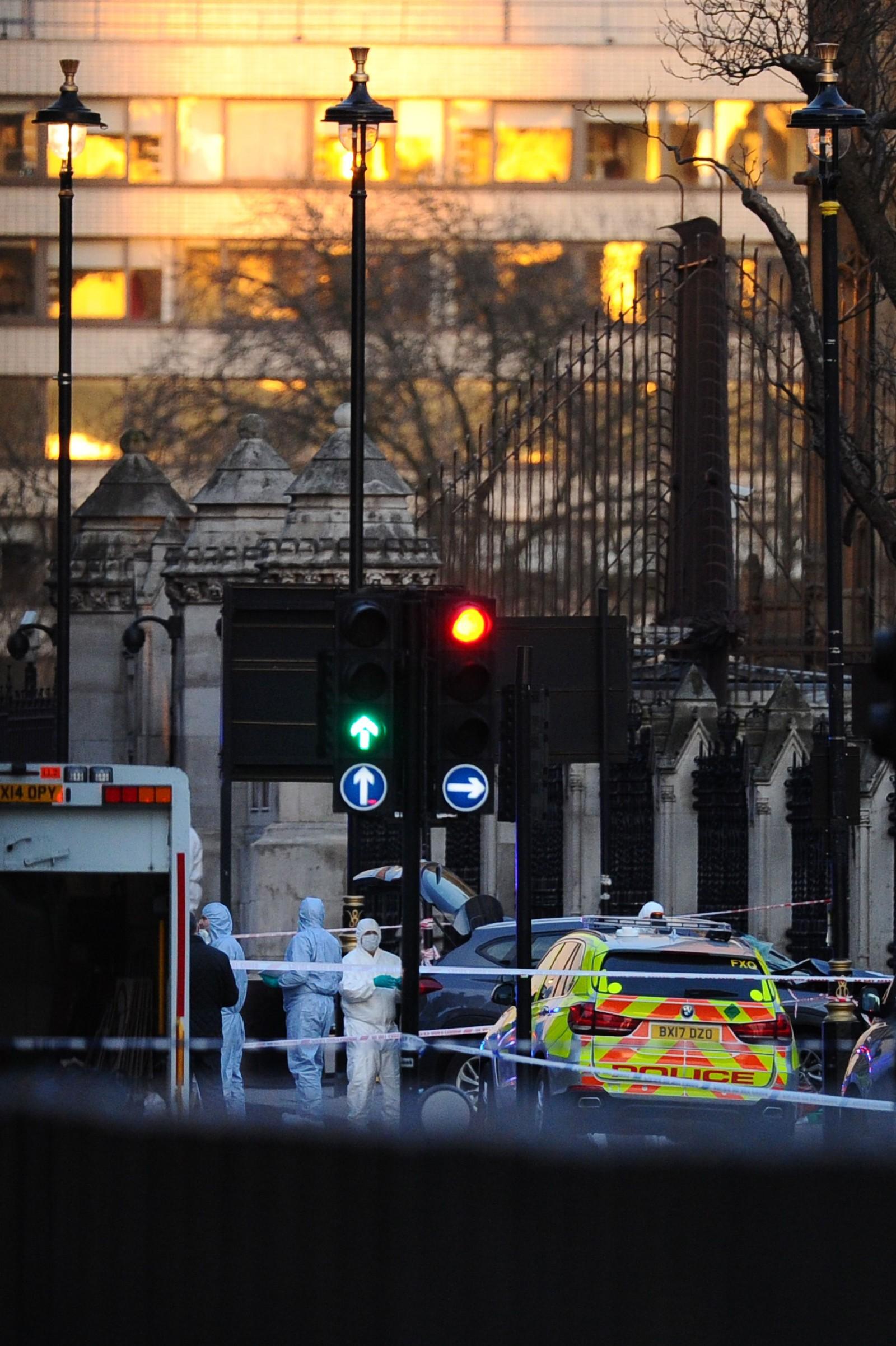 Britiske krimteknikere arbeider i nærheten av den grå bilen som krasjen inn i gjerdet rundt parlamentsbygningen.