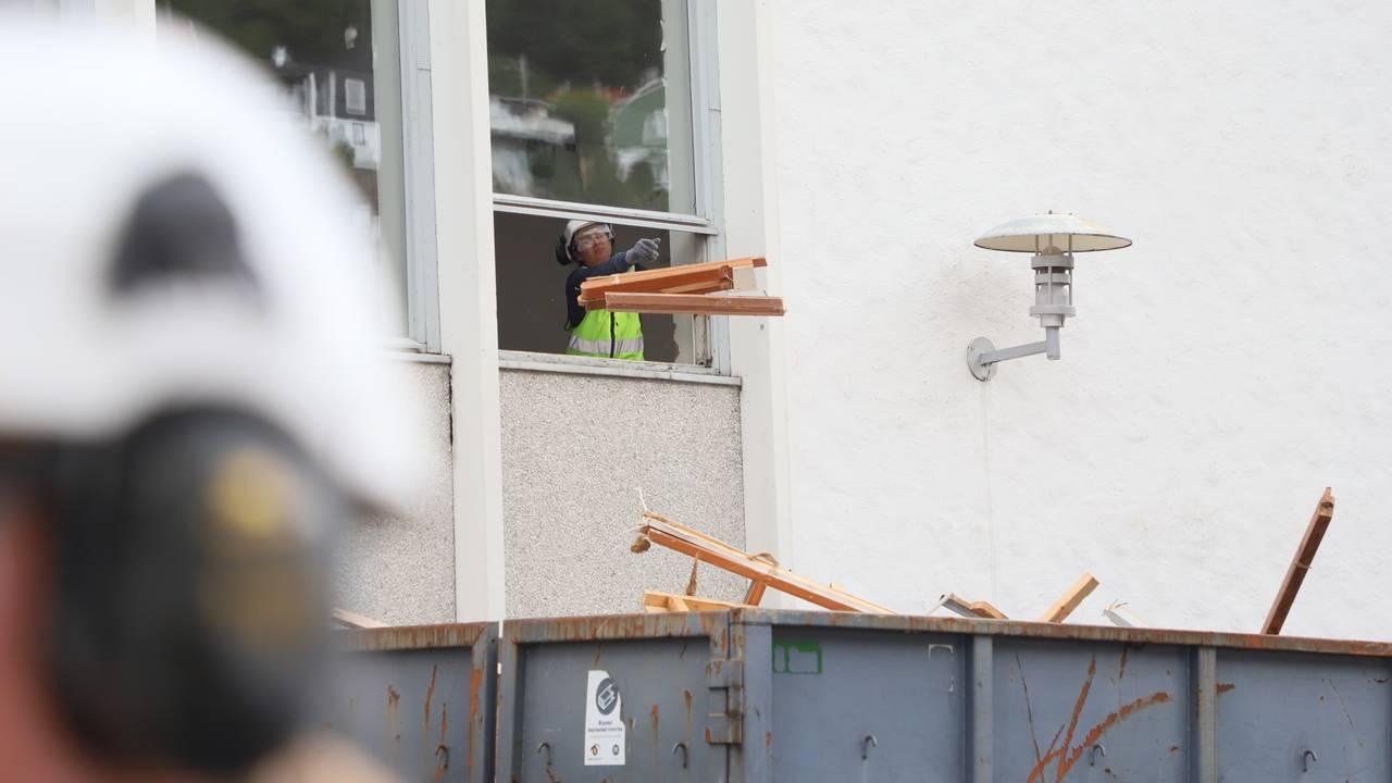 En sommervikar kaster brukte materialer og avfall ut av et vindu og ned i en container. I hjørnet av bildet ser vi hørselvernet og hjelmen til en annen sommervikar.