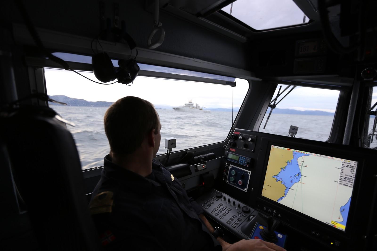 I BJØRNEFJORDEN: Kystvaktskipet Tor, som Andreas Marstrander betrakter på avstand fra lettbåten, ser kanskje liten ut på avstand, men den er nesten 50 meter lang og har 14 manns besetning.