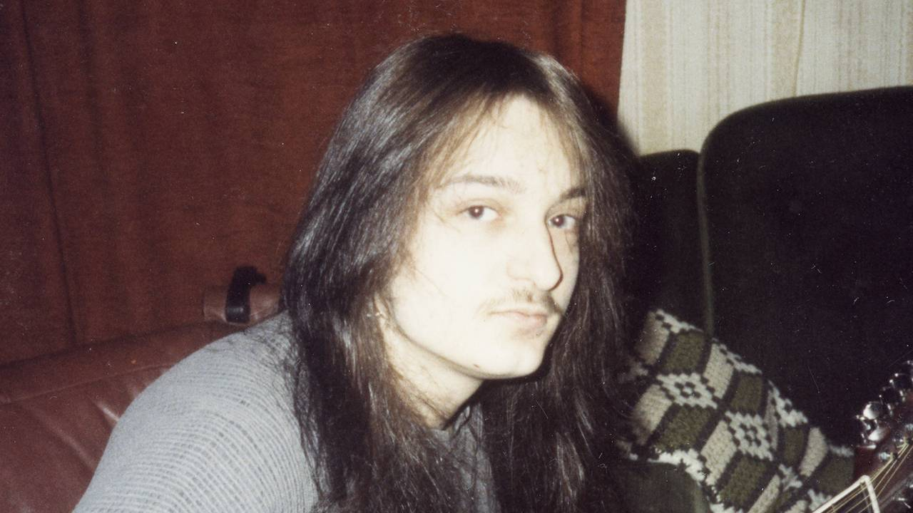 Jørn Stubberud som tenåring, med langt mørkt hår, en liten bart og en kassegitar.