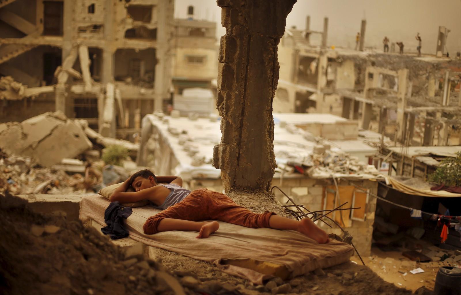 Mens en sandstorm trua Midtøsten, sov denne palestinske gutten på en madrass i ruinene av et hus som ble ramma i Gaza-krigen i fjor sommer. To personer ble drept og flere hundre skada. Stormen skal også ha satt en midlertidig stopper for kamphandlinger i Syria, og gjort det vanskelig for fly å lande på Rhodos.