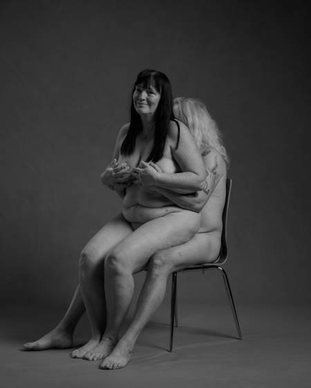 En naken dame med langt mørkt hår sitter på fanget til en naken mann med langt hvitt hår som sitter på en stol og holder henne på puppene. De er et godt voksent par.