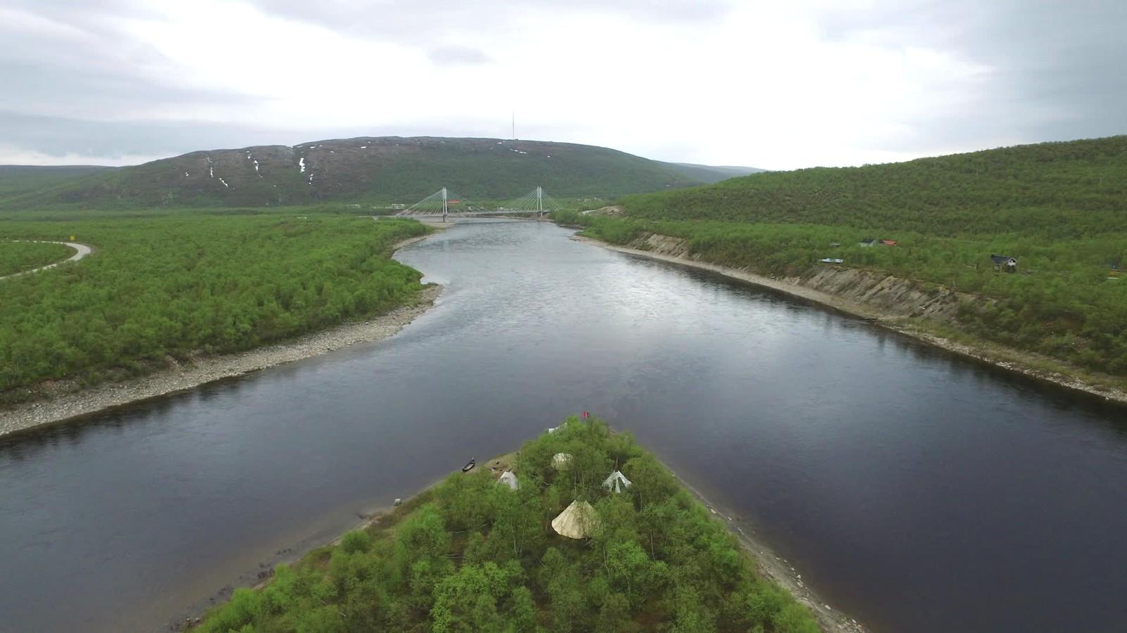 Øya Čearretsuolu i forgrunnen hvor protestleiren er etablert, og Samelandsbrua i bakgrunnen. Brua danner veiforbindelse over Tanaelva mellom Tana kommune i Norge og Utsjok kommune i Finland.