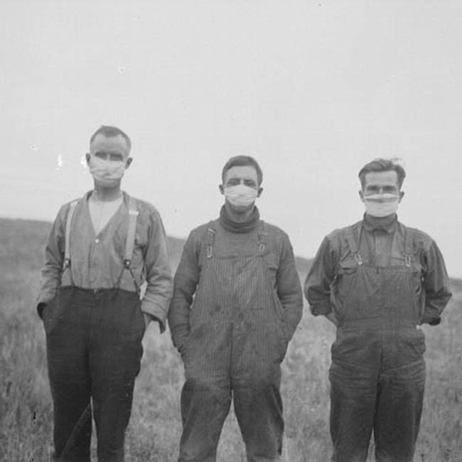 Men in an Alberta field wear masks during the Spanish flu, Fall 1918, Canada.