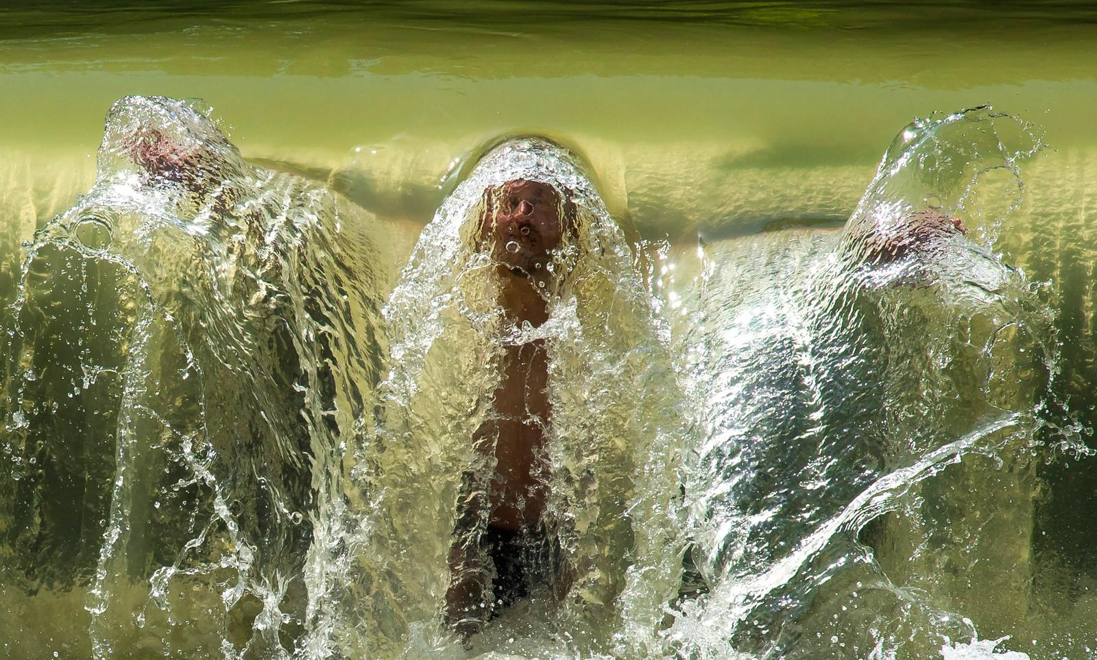 En mann holder hodet kaldt i sommervarmen i Englischer Garten i München.