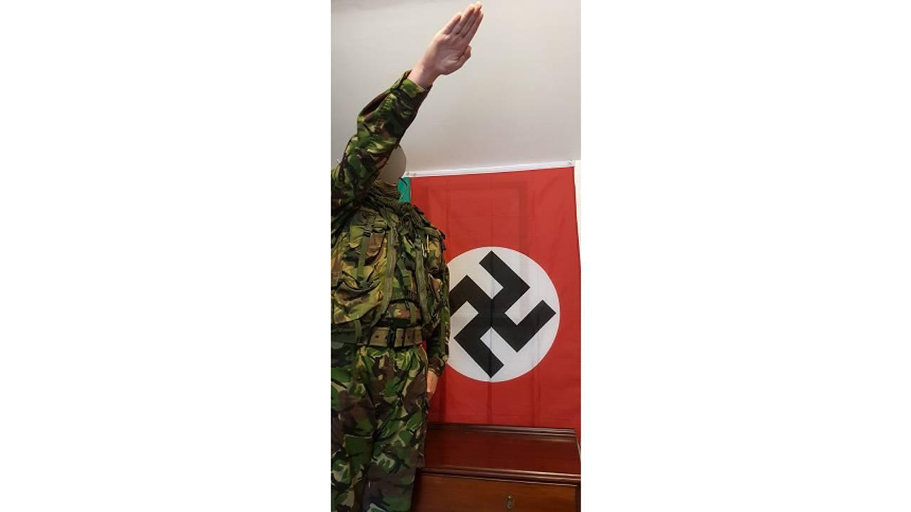 Ung britisk gutt i militærklær viser nazi-hilsen foran hakekors-flagg