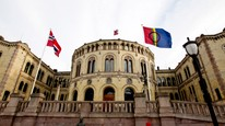 Det samiske og norske flagget vaier foran Stortinget på samenes nasjonaldag 6. februar. Foto: Scanpix/Kallestad