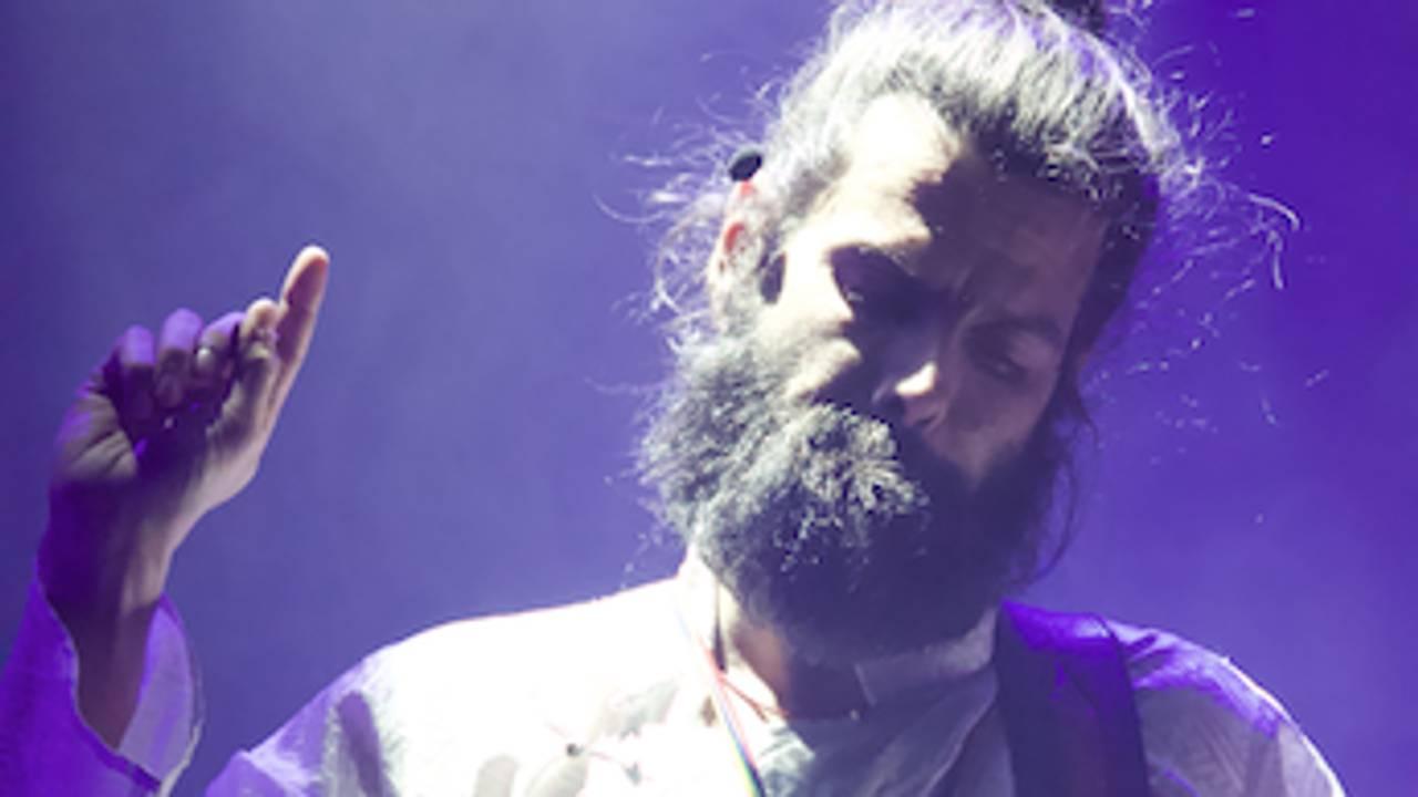 Jørgen Nøvik på scenen, i hvite klær med hånda opp