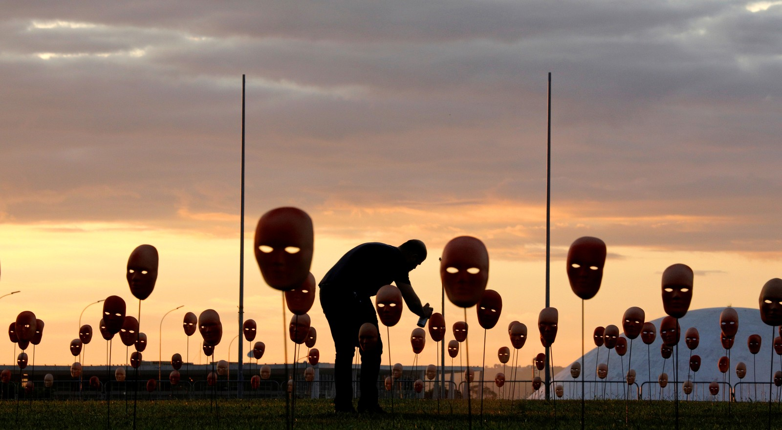 En mann maler masker foran kongressbygningen i Brasilia som er satt opp i protest mot politiske korrupsjon.