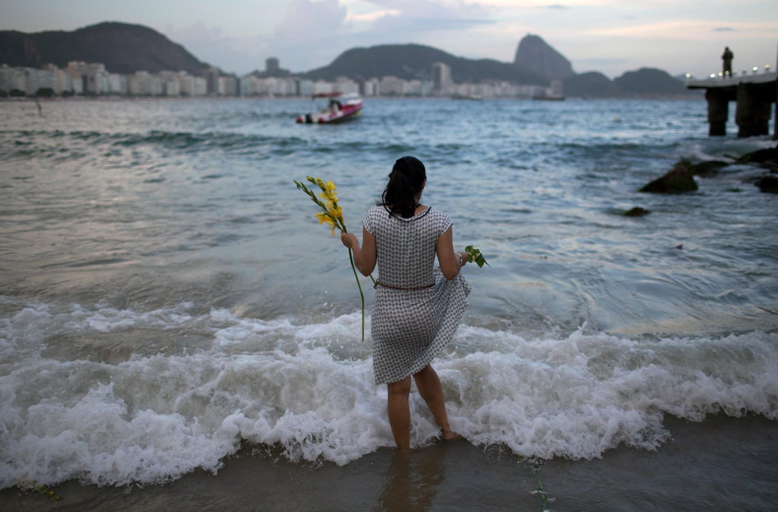 RIO DE JANEIRO: En kvinne kaster blomster på havet ved Copacabana-stranden som et offer til havgudinnen Yemanja, for å sikre seg lykke i året som kommer.