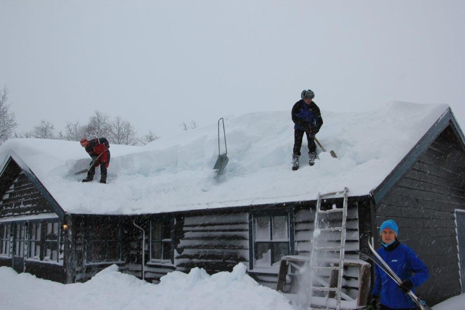 I indre Sogn var Tor snill med bygningar og skog, men i høgda kom det bra med snø i bakkant av uvêret. Her er folk i gang med å spa snø av taket på Aosahytta på Seimsåsen skisenter i Årdal søndag.