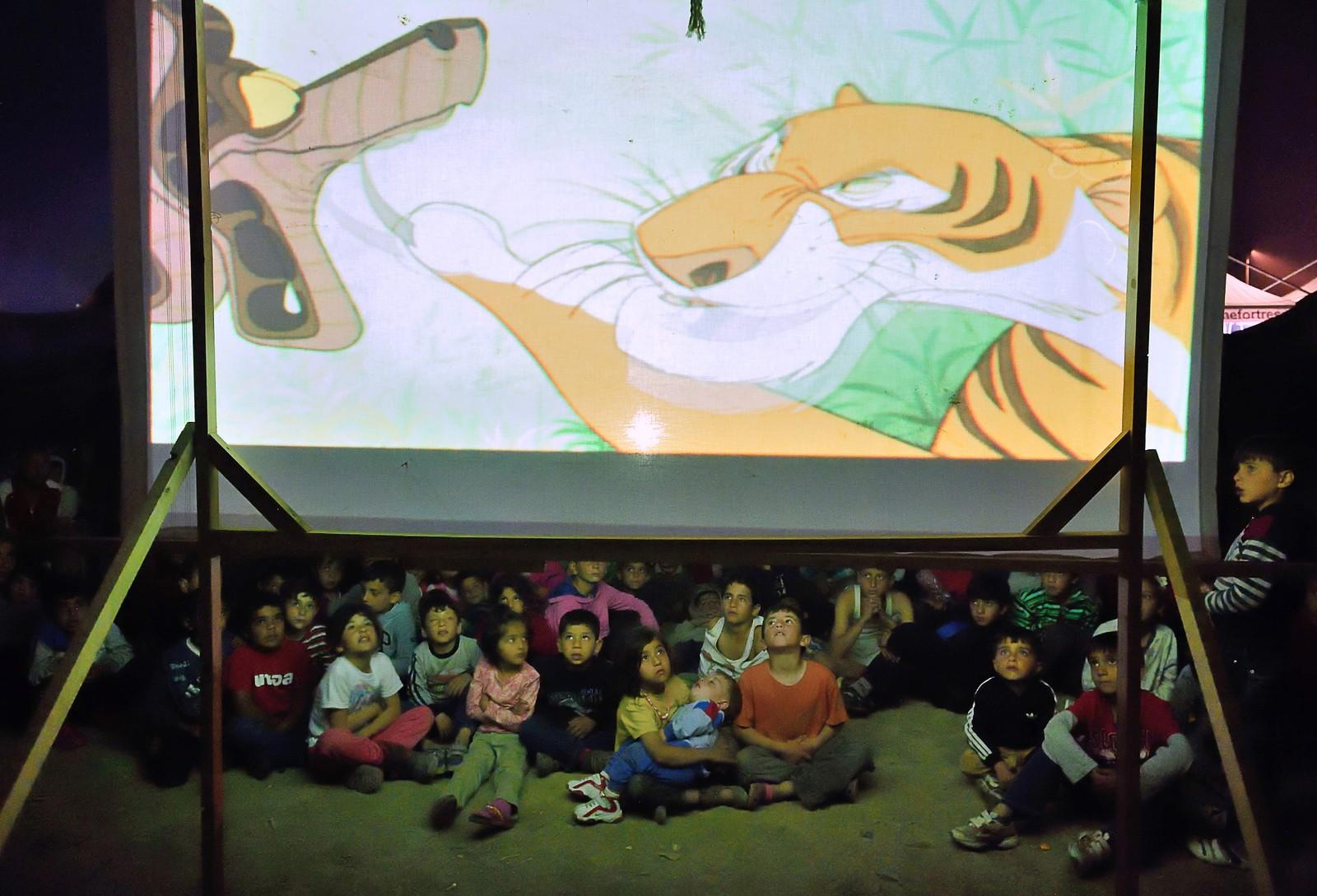 KAA OG SHERE KHAN: Barn i den midlertidige flyktningleiren ved Idomeni, på grensen mellom Hellas og Makedonia, fikk torsdag se tegnefilmen «Jungelboken» på storskjerm.