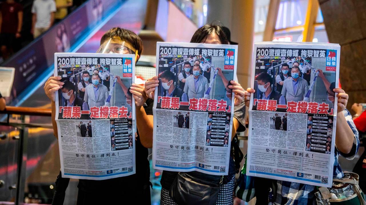 Demonstranter holder opp en kopi av avisen Apple Daily etter at politiet i Hongkong hadde ransaket avisens kontorer.