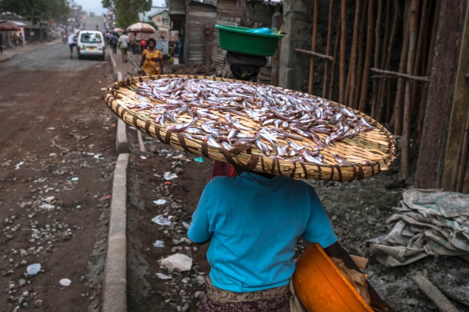 En kvinne frakter fisk gjennom gatene i Goma i Kongo den 12. juli. Det bor omtrent en million mennesker i byen som ligger ved Kivusjøen.
