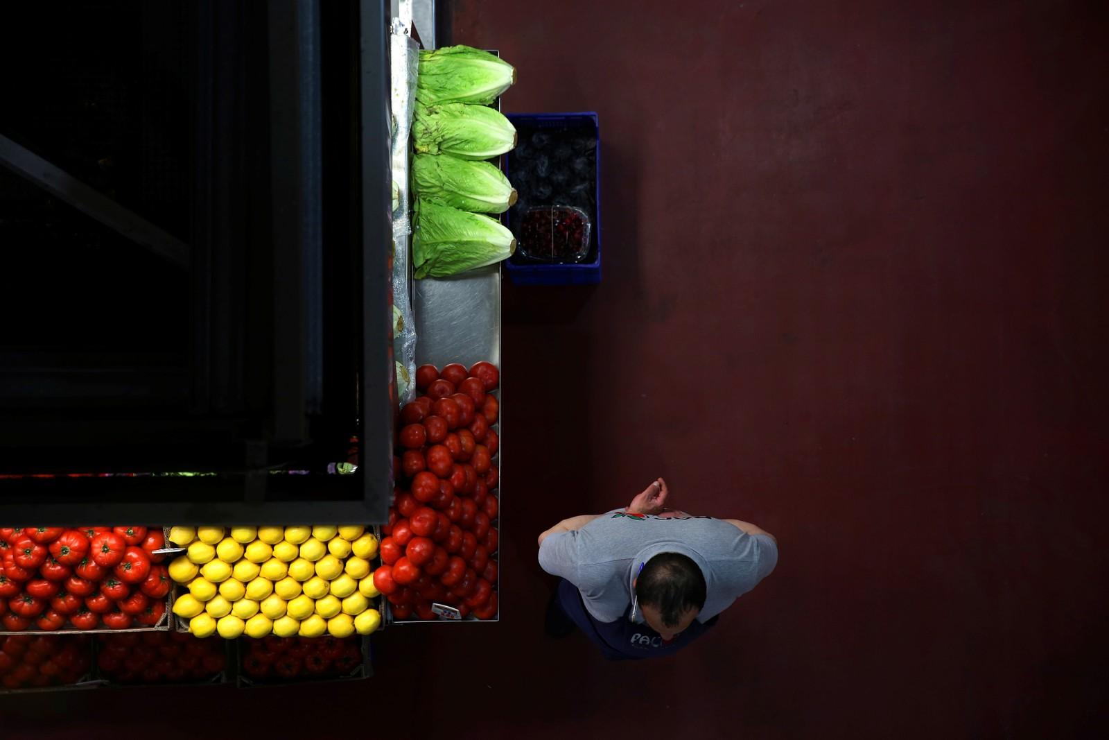 En mann og grønnsakene han selger i Madrid i Spania.