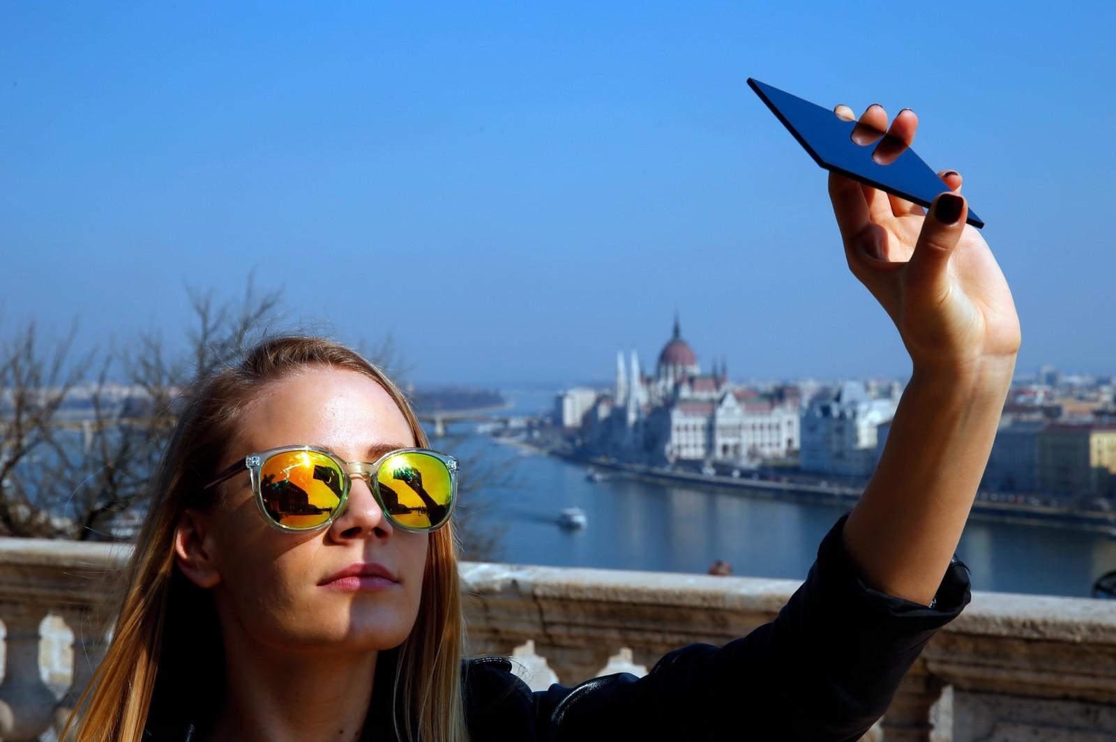 En kvinne ser på sola gjennom en mørk glassplate i Budapest.
