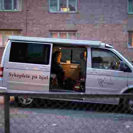 Bilen til sykepleie på hjul venter utenfor bygård.
