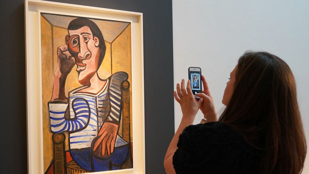 "(FILES) In this file photo taken on May 3, 2018 a Christie's employee takes a picture of Pablo Picasso's ""Le Marin"" during a media preview at Christie's in New York.A Picasso self-portrait estimated to be worth $70 million and due to go under the hammer in New York on May 15, 2018, has been ""accidentally damaged"" and withdrawn from auction, Christie's said. The 1943 masterpiece called ""The Marin"" or ""The Sailor"" had been a highlight of Christie's marquee impressionist and modern evening art sale. According to US media, it belongs to former casino magnate Steve Wynn.Christie's said the damage happened on Friday ""during the final stages of preparation.""/ AFP PHOTO / Don EMMERT / RESTRICTED TO EDITORIAL USE - MANDATORY MENTION OF THE ARTIST UPON PUBLICATION - TO ILLUSTRATE THE EVENT AS SPECIFIED IN THE CAPTION"