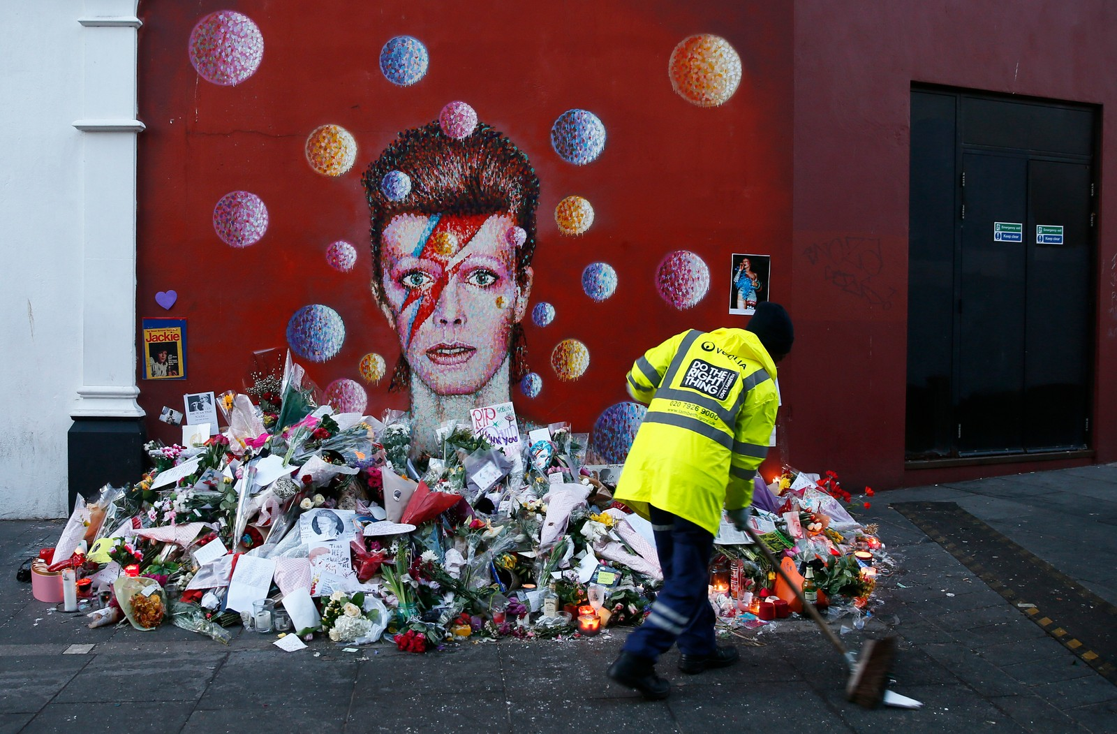 En arbeider feier gata foran et veggmaleri av artisten David Bowie i Brixton, Sør-London, 12.januar. Mange la ned blomster etter at det ble kjent at den verdenskjente artisten døde av kreft bare dager etter lanseringen av hans nye album.
