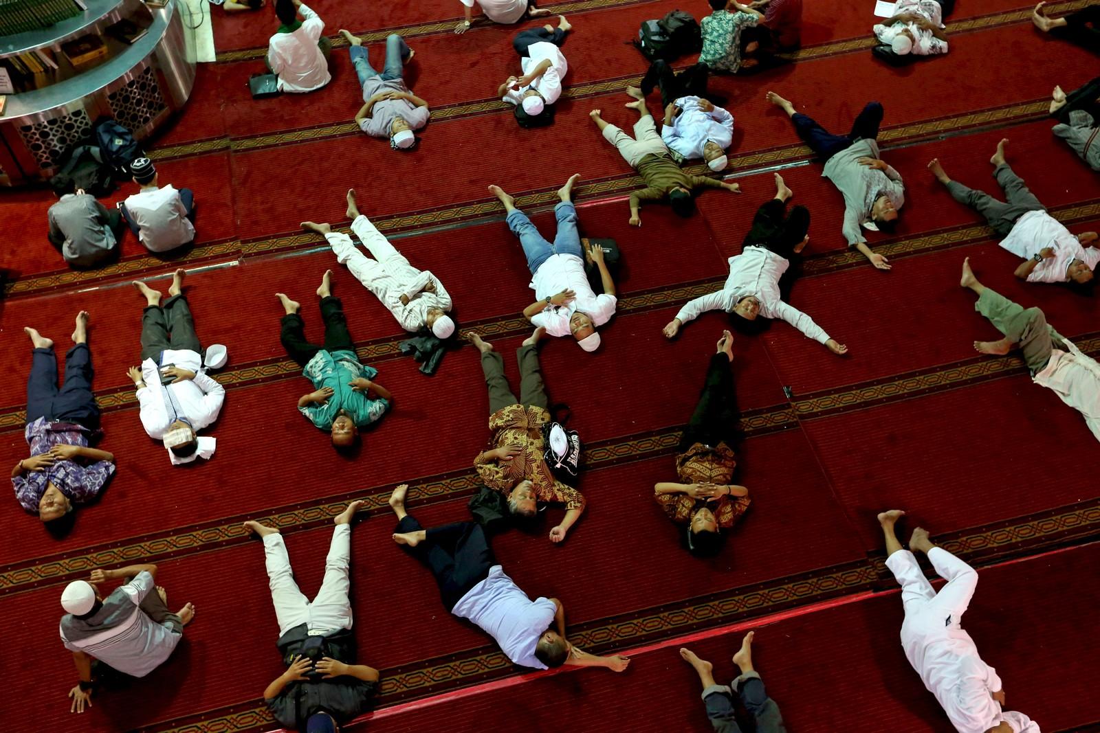 Muslimske menn hviler og venter på kvelden under fasten i Jakarta.
