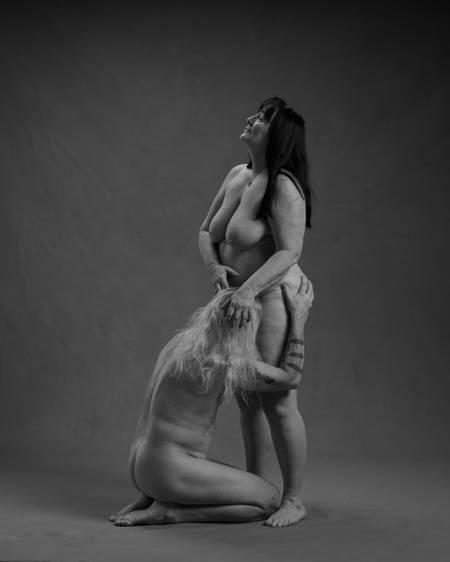 En eldre mann med langt hvitt hår sitter på kne og simulerer oralsex på en eldre kvinne med mørkt langt hår. Begge er nakne. Kjønnsorganene er ikke synlige. De er et godt voksent par.