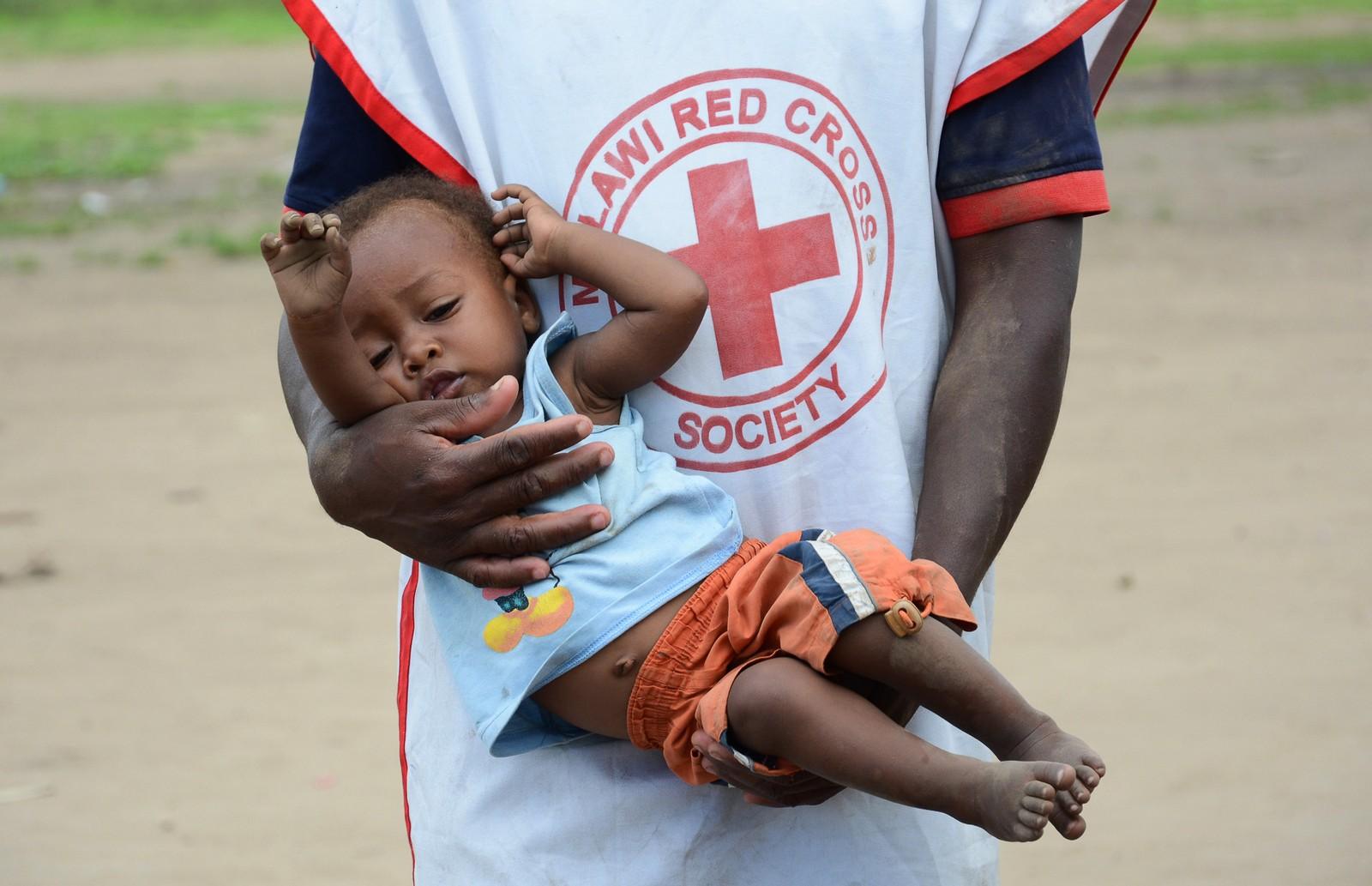 En helsearbeider tar hånd om et barn som ble funnet gående alene nær en flyktningleir i Chikwawa-distriktet.