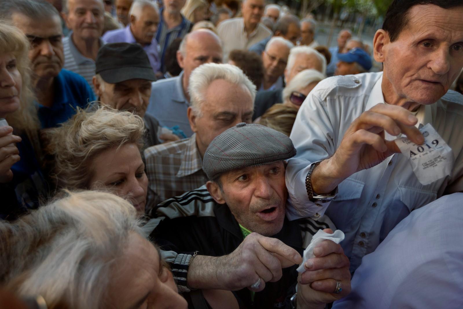 Pensjonister med kølapper forsøker å komme seg inn i en bank i Aten for å få ta ut penger.