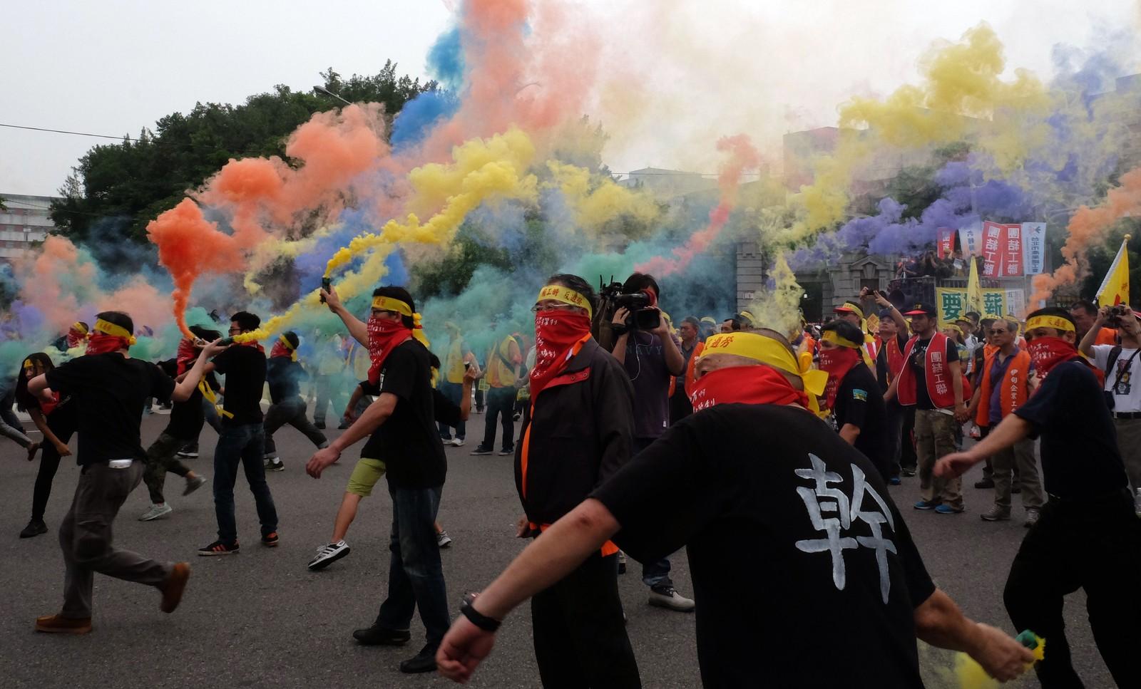 Arbeidere kaster røykbomber i Taipei i Taiwan 1. mai. Tusener tok til gatene i Taipei for å kreve bedre arbeidsvilkår av myndighetene i landet.