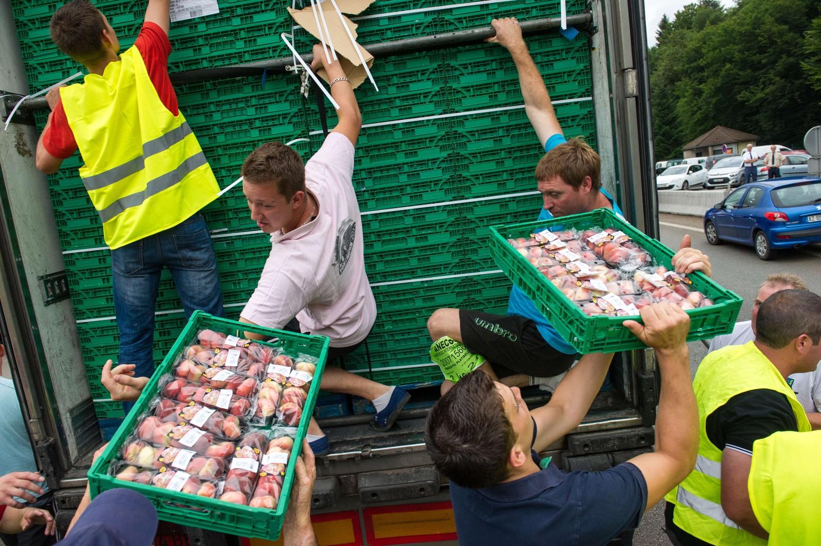 Protesterende bønder tømmer en lastebil med frukt i L'Isle-sur-le-Doubs.