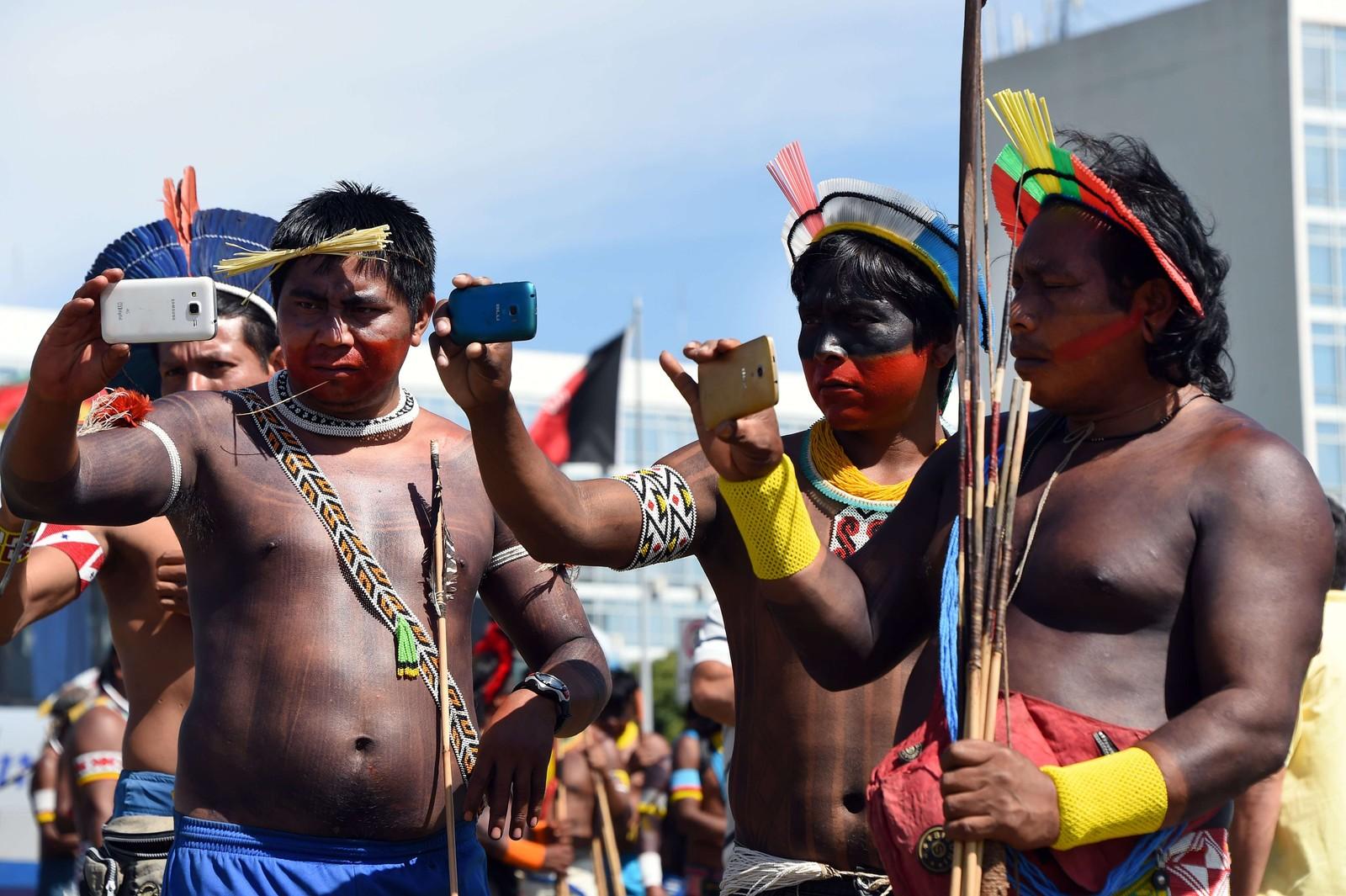 Medlemmer av Kayapo- og Pataxo-stammene tar selfies under en demonstrasjon foran den brasilianske kongressen, mens de folkevalgte diskuterer stammenes landområder.