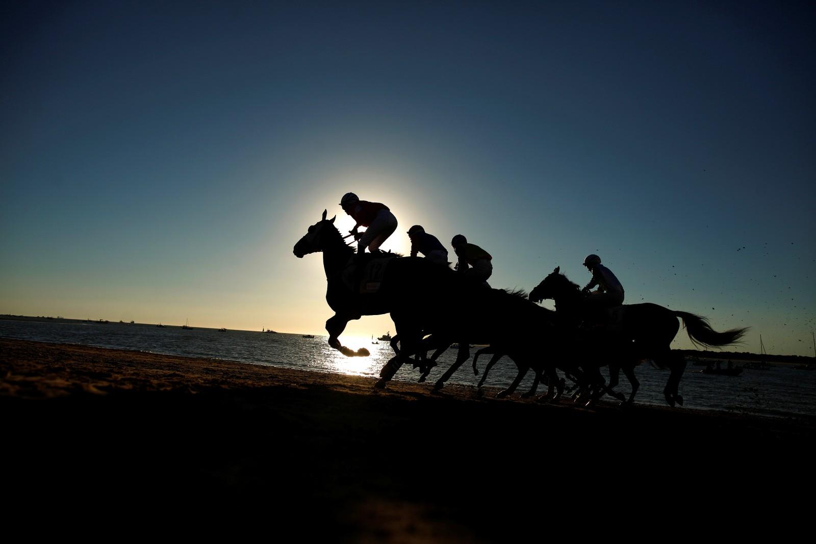 Hesteløp på en strand i Sanlúcar de Barrameda i Spania.