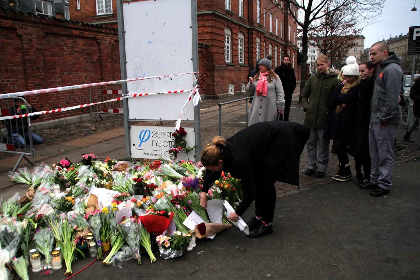 En sørgmodig stemning preger stedene, og folk holder rundt hverandre og legger ned blomster foran Krudttønden i København.